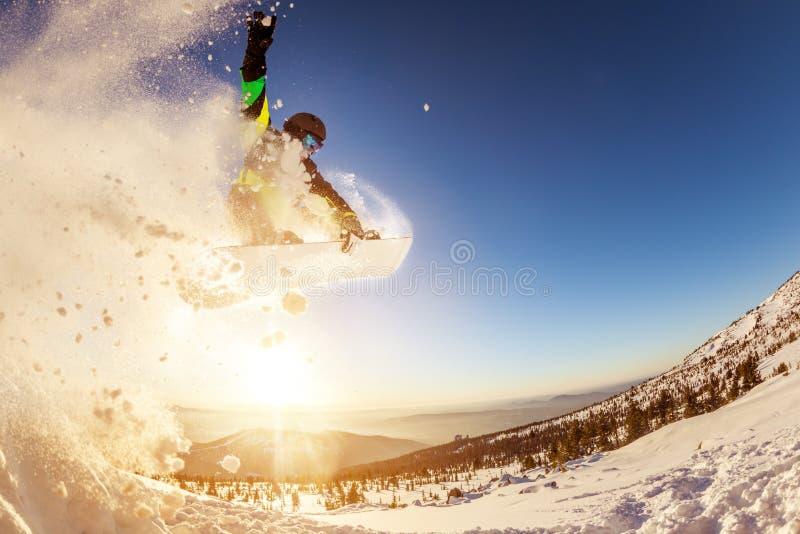 挡雪板跳反对日落太阳 免版税库存图片