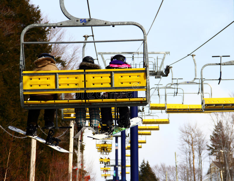 挡雪板&滑雪者家庭在驾空滑车 免版税库存图片
