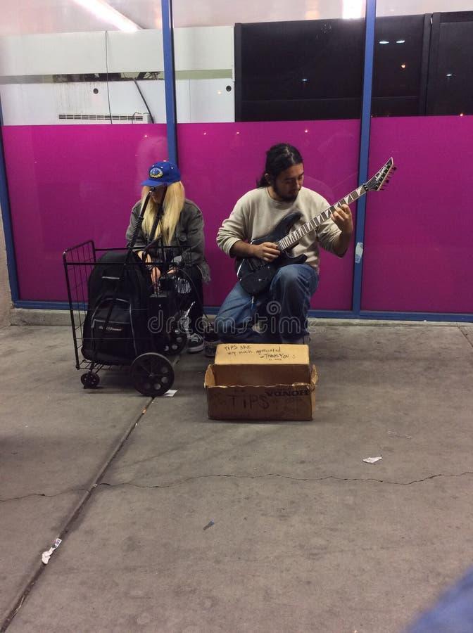 挣弹他的吉他的额外金钱在街道 库存图片