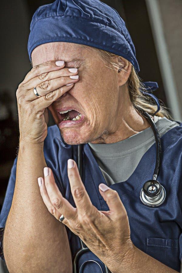挣扎的哭泣的女性医生或护士 库存图片