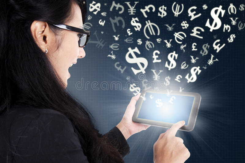 挣金钱的女实业家网上与片剂 免版税库存图片