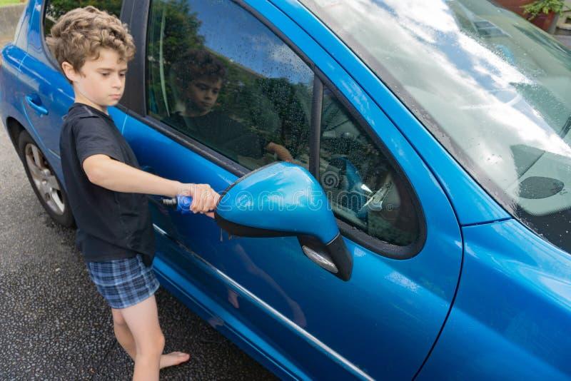 挣零花钱的男孩清洗蓝色小型客车 库存图片