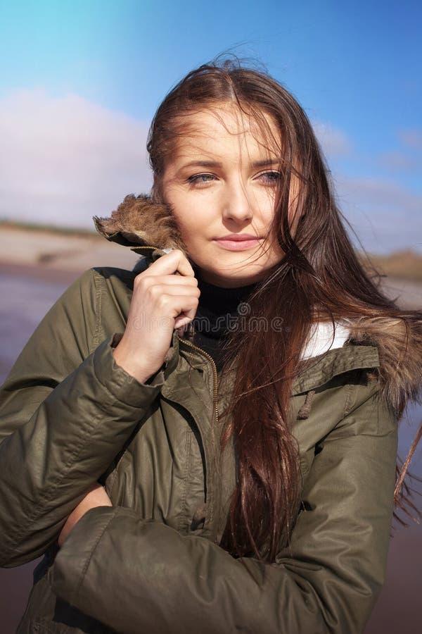 挤作一团在她的外套的美丽的少妇 库存图片