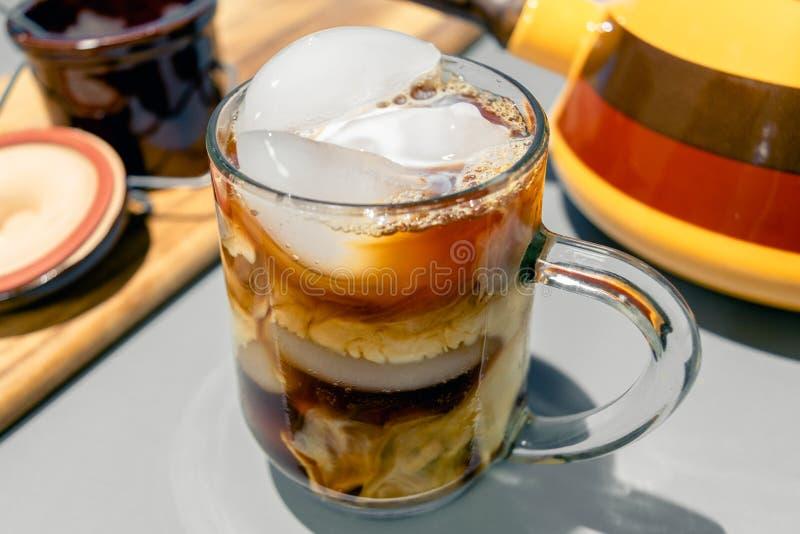 挤奶打旋在一个冷的杯子被冰的咖啡 库存图片