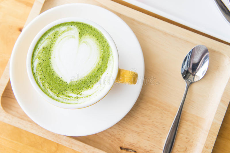 挤奶热的绿茶和咖啡店并且结块草莓蛋糕 免版税库存图片