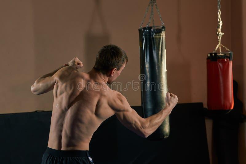 挥剧烈和强有力的拳的运动拳击手 肌肉人照片健身房的 免版税库存照片