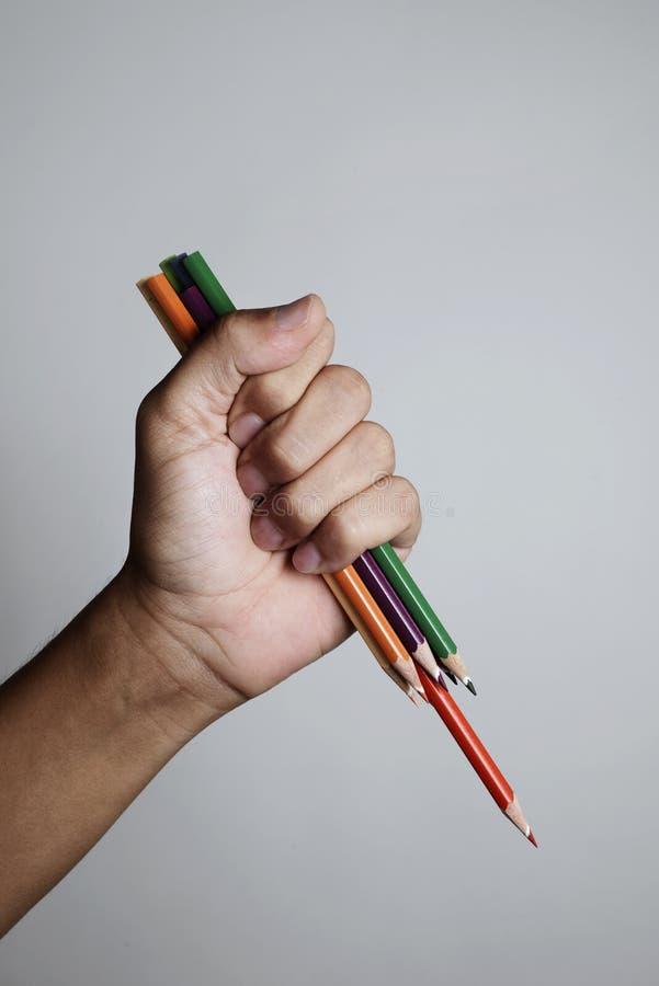 挥动一些被削尖的铅笔蜡笔的年轻人 库存图片