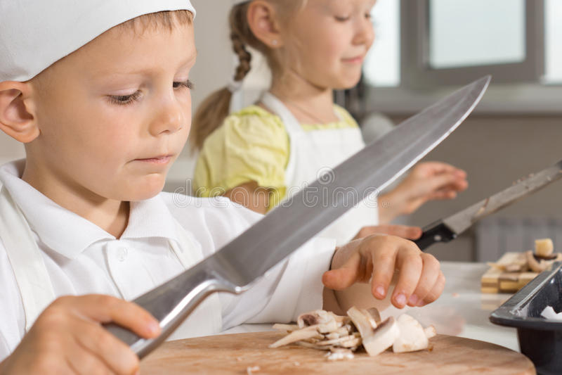 挥动一把大刀子的小男孩砍蘑菇 免版税库存照片