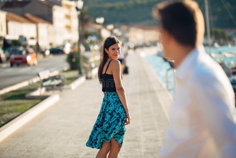 挥动与在街道上的一个人的年轻可爱的妇女 回顾在一个英俊的人的私秘微笑的妇女 女性吸引力 库存照片