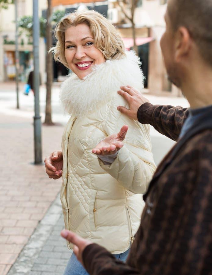 挥动与微笑的宜人的白肤金发的妇女的老人 免版税图库摄影