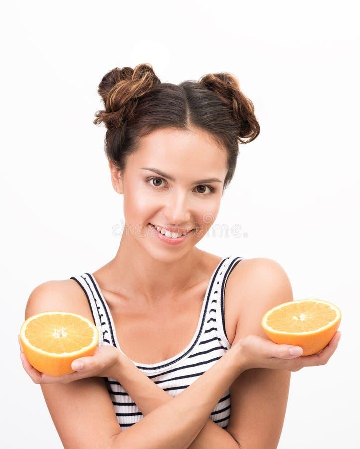 挥动切片桔子的画象年轻精力充沛的妇女的 胳膊克服 库存照片