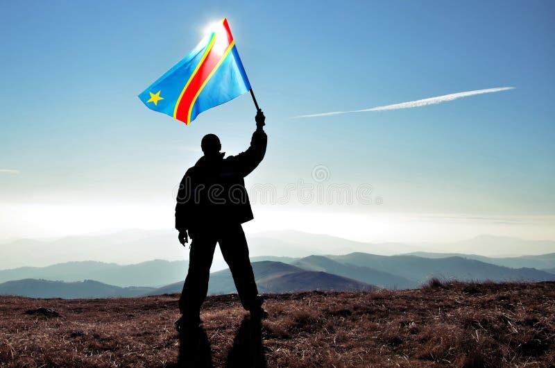 挥动刚果民主共和国旗子的成功的剪影人优胜者在山顶部 库存照片