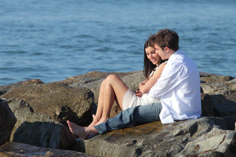 挥动和拥抱在海旁边的夫妇 库存照片