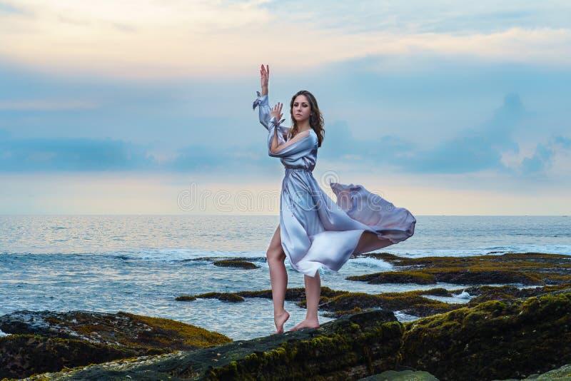 挥动在与深刻的领口逗留的风的美丽的长的礼服的典雅的年轻女人在岩石的海洋海滩在日落 免版税库存图片