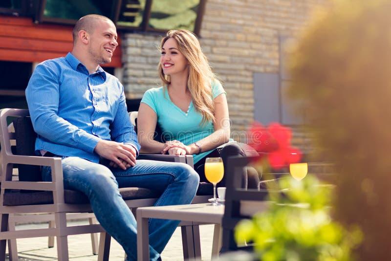 挥动在咖啡馆 坐在咖啡馆的美好的爱恋的夫妇享用在咖啡和交谈 爱,浪漫史,约会 免版税库存照片