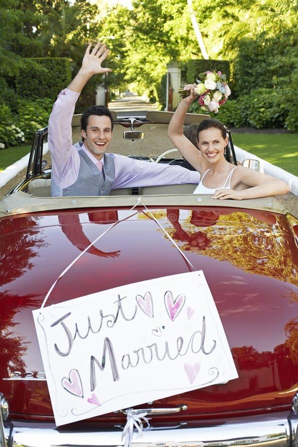挥动在敞篷车汽车的新婚佳偶夫妇 免版税库存照片
