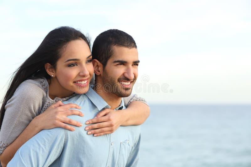 挥动在海滩的爱的阿拉伯夫妇 库存照片