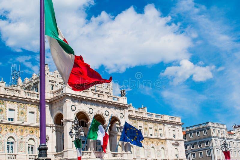 挥动在的里雅斯特老镇的意大利旗子在有风晴天 库存照片