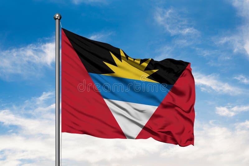 挥动在风的安提瓜和巴布达旗子反对白色多云天空蔚蓝 库存图片