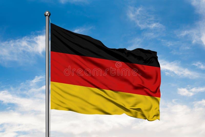 挥动在风的德国的旗子反对白色多云天空蔚蓝 德国旗子 免版税库存照片