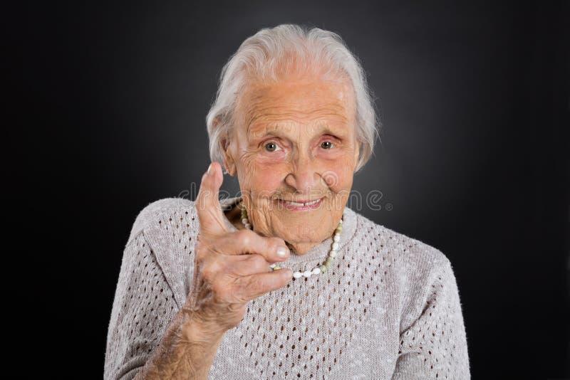挥动她的手指的微笑的老妇人 免版税库存照片