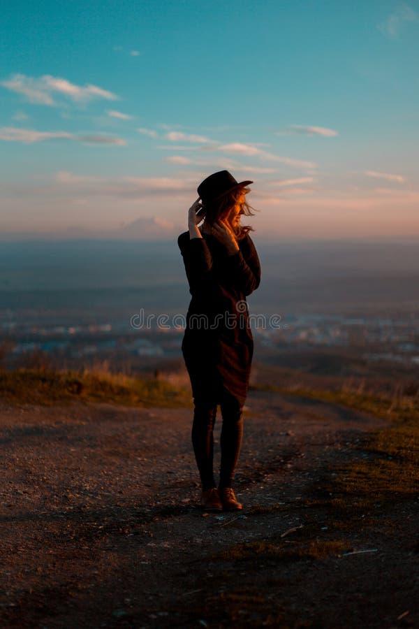 挥动她的有她的后面的女孩帽子面对与山的谷 Aunset 库存照片