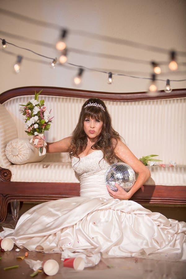 挥动婚礼花束的生气新娘 库存图片