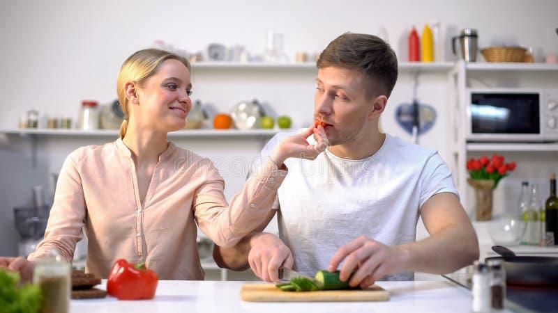挥动年轻的幸福家庭,有未加工的蔬菜的妻子哺养的丈夫,eco食物 免版税库存照片