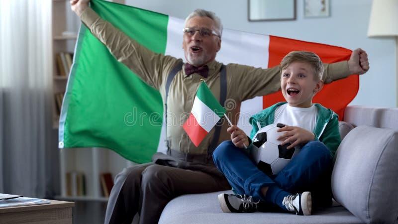 挥动意大利旗子的爷爷,与男孩一起庆祝足球队员胜利  库存图片