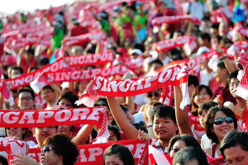 挥动新加坡围巾的听众在NDP期间2012年 库存图片
