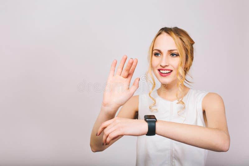 挥动用她的手和摆在与微笑的俏丽的年轻金发夫人隔绝在白色背景 迷人的女孩 免版税库存图片