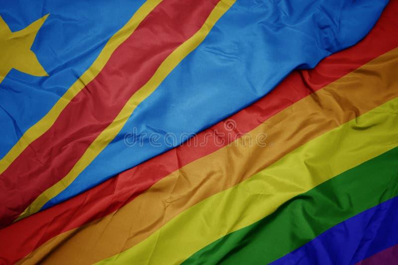 挥动的五颜六色的快乐彩虹旗子和刚果民主共和国的国旗 免版税库存照片