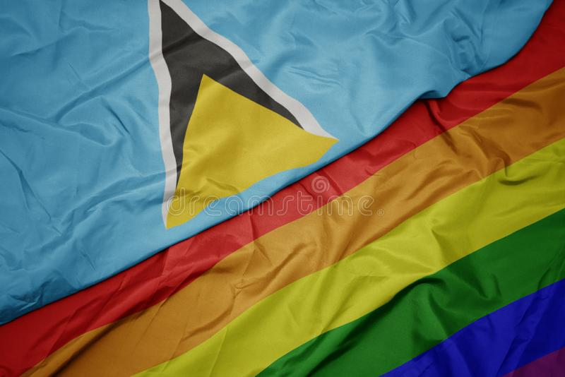 挥动的五颜六色的快乐彩虹旗子和圣卢西亚的国旗 免版税库存图片