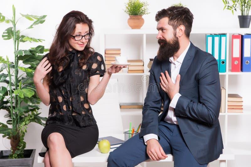 挥动的同事 有胡子的男人和可爱的妇女 男人和妇女交谈咖啡时间 办公室谣言 E 库存照片