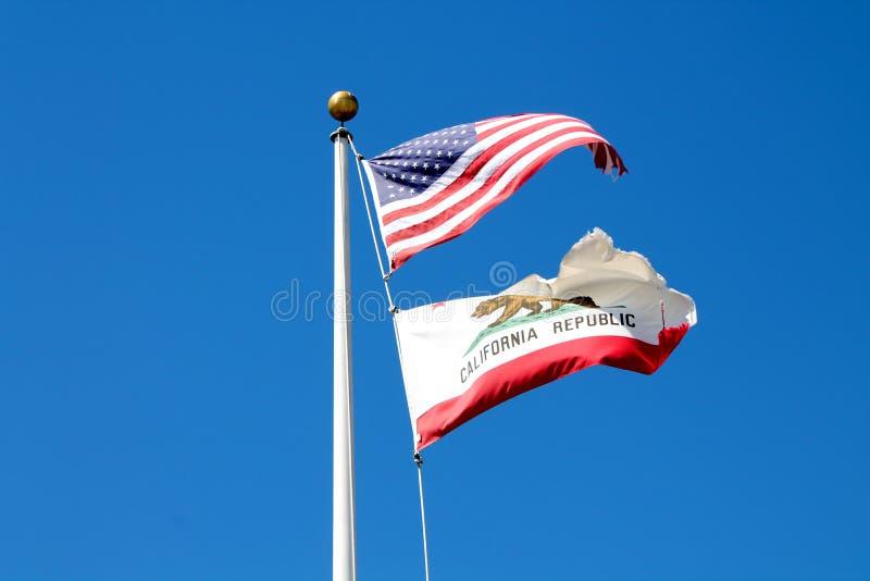 挥动的美国人和加利福尼亚陈述在微风的旗子在明亮的蓝天下 免版税库存照片