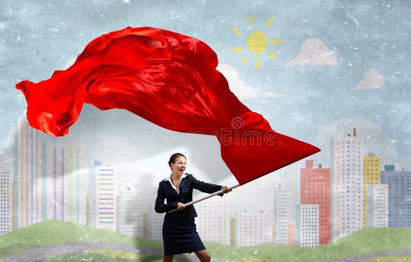 挥动红旗的妇女 库存照片
