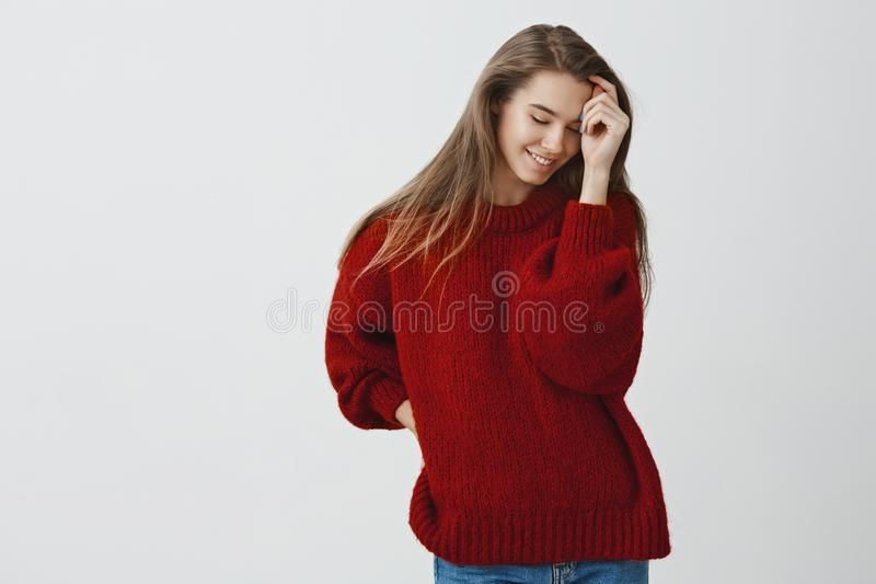 挥动红色宽松温暖的毛线衣的肉欲和浪漫妇女,摆在嫩和逗人喜爱微笑的害羞看下来,接触 免版税图库摄影