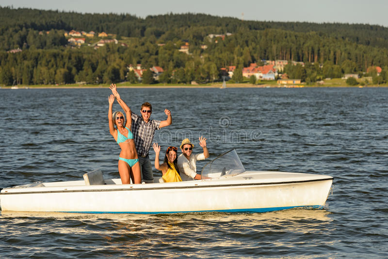 享受在速度小船的年轻朋友夏天 免版税库存图片