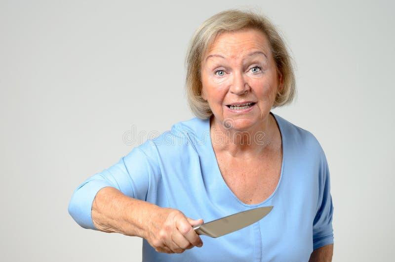 挥舞厨刀的年长妇女 库存照片
