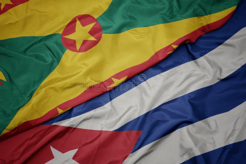 挥舞着五颜六色的古巴国旗和格林纳达国旗 免版税库存照片