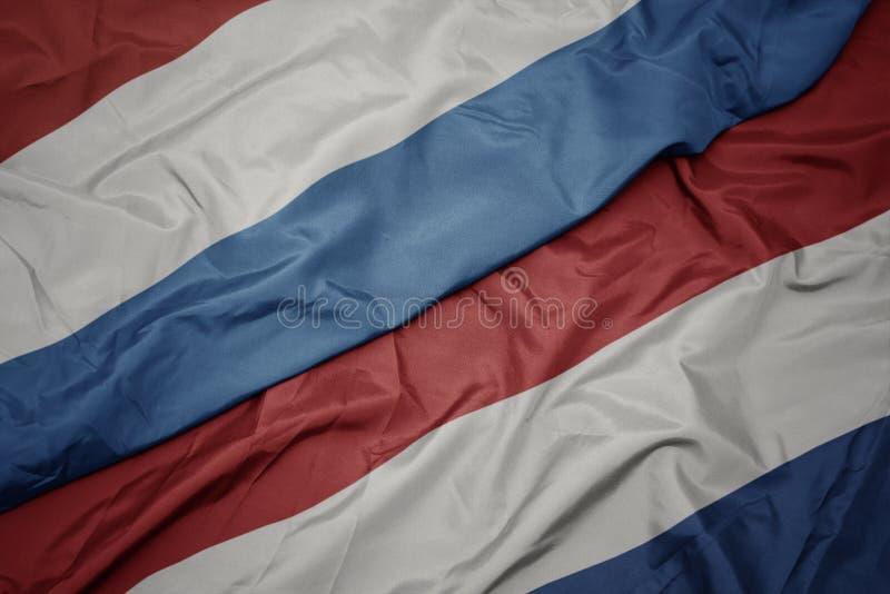 挥舞着荷兰彩旗和卢森堡国旗 免版税图库摄影