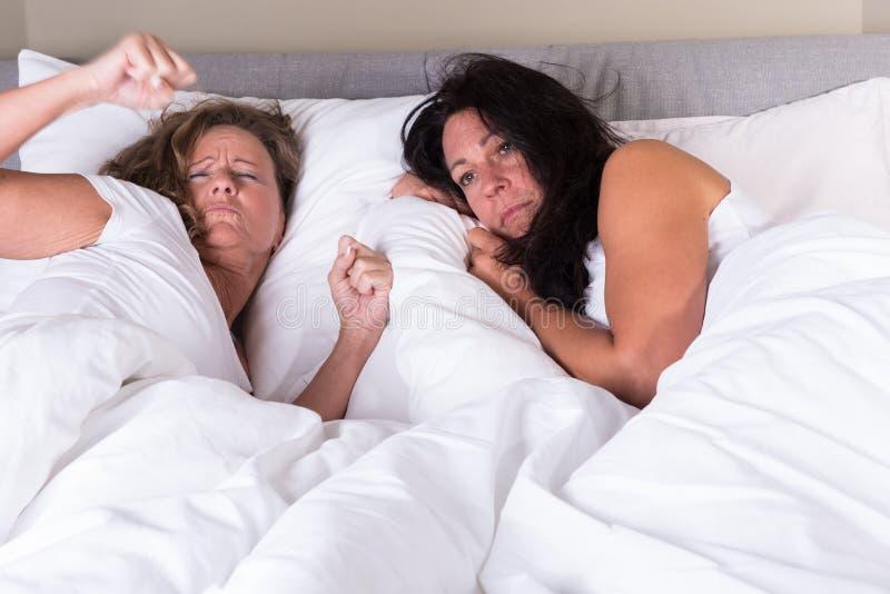 紧挨着醒在床上的两名可爱的妇女 免版税库存图片