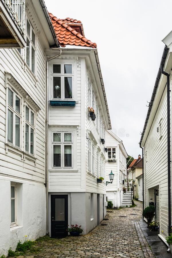 挪威卑尔根一条狭窄舒适街道的垂直照片,有典型的木屋 库存图片