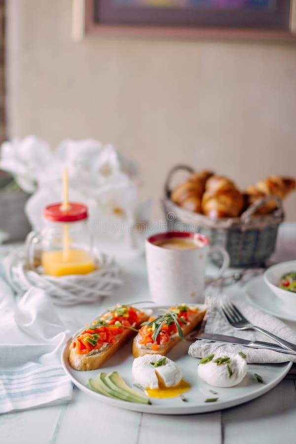 挪威早餐敬酒用在白色木桌上的三文鱼,熟蛋用沙拉,咖啡、橙汁过去和新月形面包 库存照片