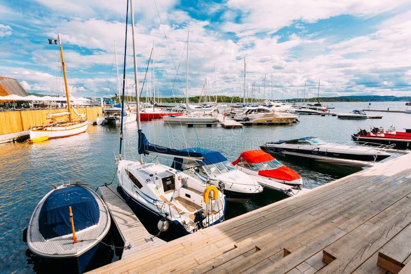 挪威,奥斯陆, Aker Brygge区 有被停泊的小船的木海码头 免版税库存图片
