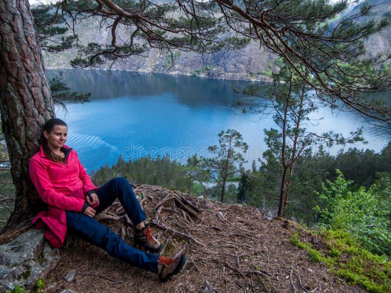 挪威-倾斜在三的女孩俯视海湾 库存照片