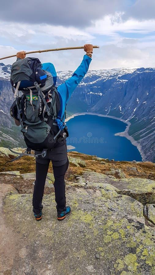 挪威-年轻人用棍子和在湖的看法山的 免版税图库摄影