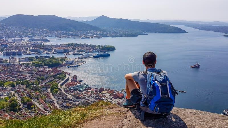 挪威- sittting在一个岩石的年轻人,有在卑尔根的看法 免版税库存照片