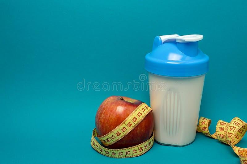 振动器与蛋白质鸡尾酒苹果计算机和卷尺健身饮食体育生活 免版税库存图片