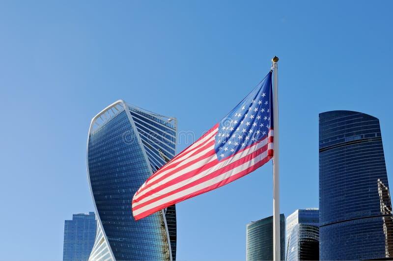 振翼在旗杆的美国旗子以莫斯科市为背景 免版税图库摄影